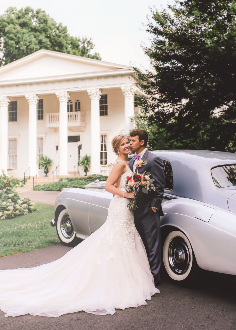 Married couple standing next to a car in front of a historic farm house.