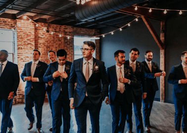 Wedding party wearing navy suits in a brick reception hall.