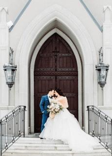 Wedding groom wearing Mystic Blue Tux with Bride in front of church doors.