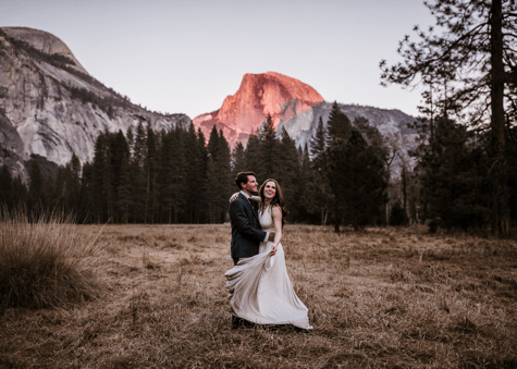 Bride and groom standing in front of a mountain.