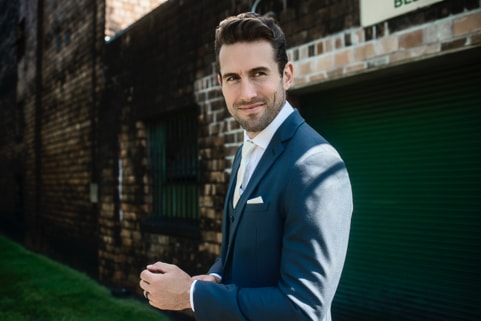 Groom in a Mystic Blue suit in front of a brick wall.