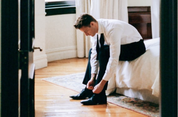 Groom tying his shoes while getting dressed in a bedroom.
