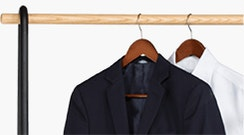 Black suit and white shirt on a clothes rack.