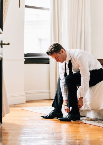Groom getting dressed in a black tux rental.