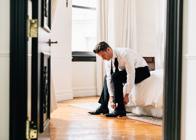 groom putting on his shoes and generation tux black tux in his bedroom