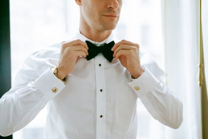 Groom trying on bowtie