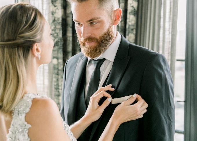 Bride adjusting pocket square on Groom wearing Black Peak Lapel Tuxedo from Generation Tux