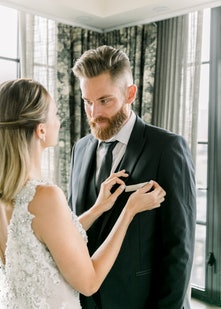 Bride adjusting pocket square on Groom wearing Black Peak Lapel Tuxedo from Generation Tux