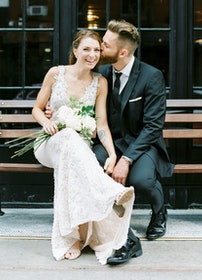 Wedding couple sitting on bench. Man wearing peak lapel black tuxedo.