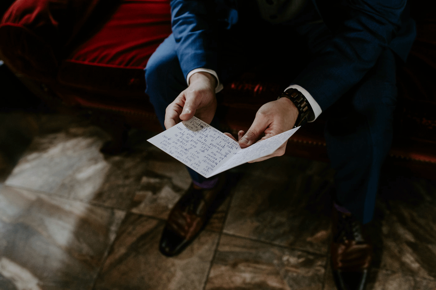 groom in blue suit reading letter from bride