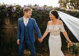 Bride and groom holding hands in garden.