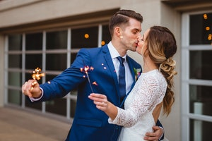 Bridge and groom kissing while holding sparklers.