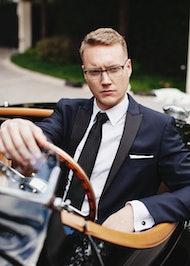 Man in tux driving a classic car