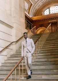 Gentlman wearing light gray suit, coming down some stairs