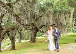 Groom taking a bride for a walk under a tree