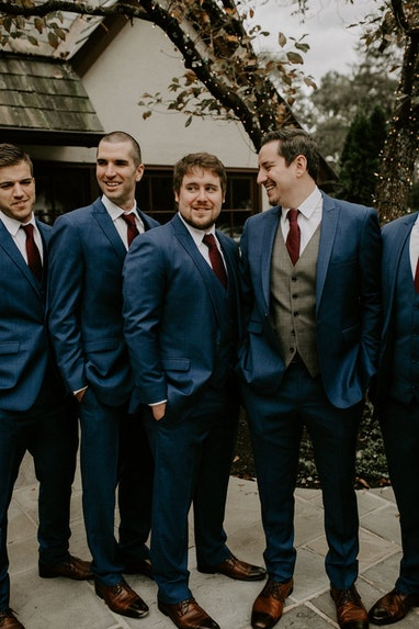Groom and groomsmen having a laugh outside