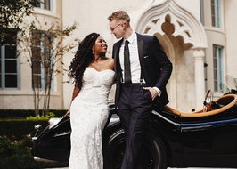 Bride and groom posing in front of car