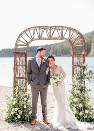 Bride and groom under lakeside alter