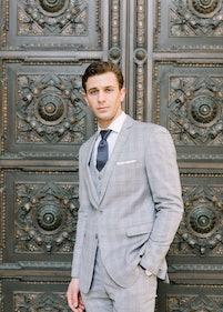 Man in gray posing in front of intricate door