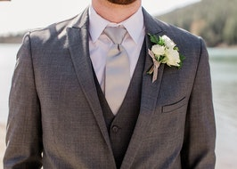 Groom wearing gray suit and vest by the lake
