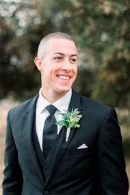 Groom wearing charcoal suit looking to bride