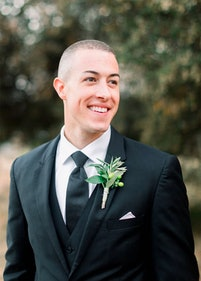 Groom wearing charcoal suit looking to bride