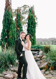 Newly married couple smiling in front of stone fountain