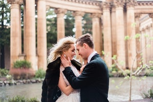 Bride and Groom embracing amoung stone columns.