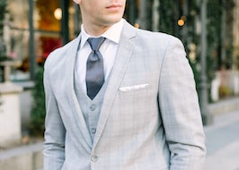 Man in gray plaid suit and vest walking around town
