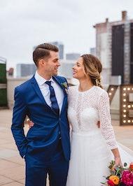 Bride and groom posing on rooftop.