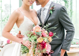 Closeup of groom in gray tux and bride holding bouquet