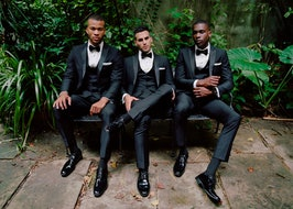 Groom, best-man and groomsmen sitting on a bench in a garden