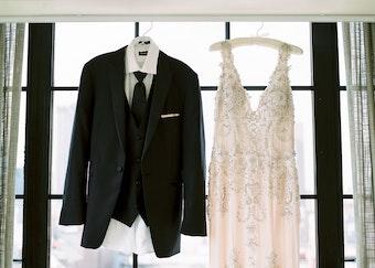 Peak lapel Black tux hanging new to wedding dress in window
