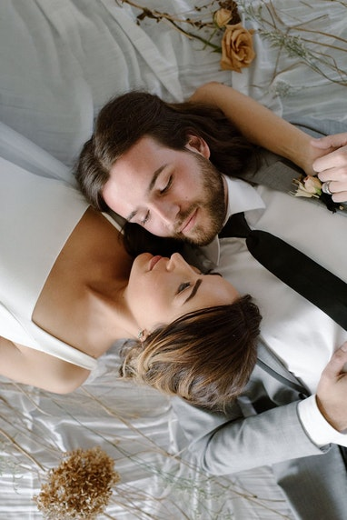 Bride and groom laying next to one another