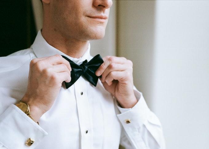 Groom fixing Generation Tux Suit Rental