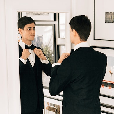 groom getting dressed in black tuxedo rental