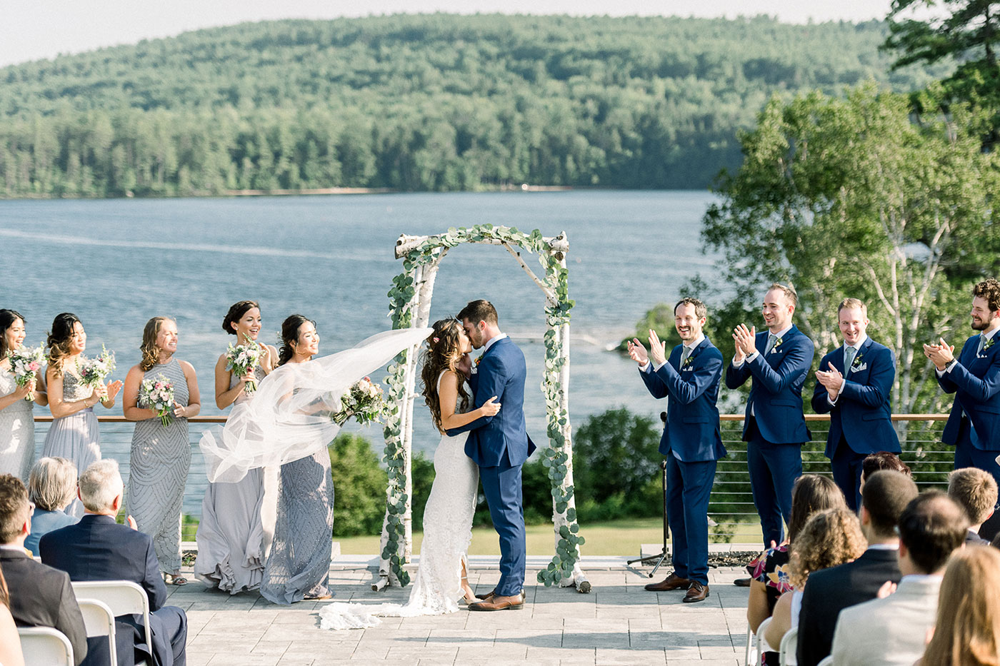 bride and groom share kiss at wedding  on lake