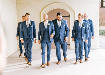 a groom and his groomsmen walk smiling in their big and tall generation tux blue suits