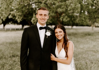 Tall groom in a black generation tux tuxedo stands outside with his bride