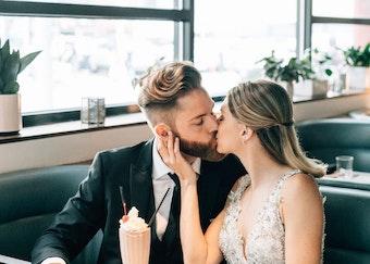 Bride and groom kissing at diner while groom wearing black peak lapel tuxedo.