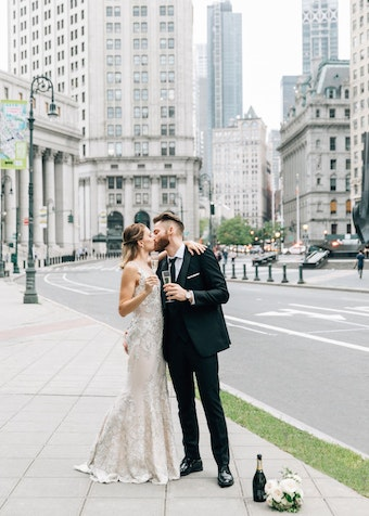 Bride and groom drinking champagne in New York City. Groom wearing black peak lapel tuxedo.
