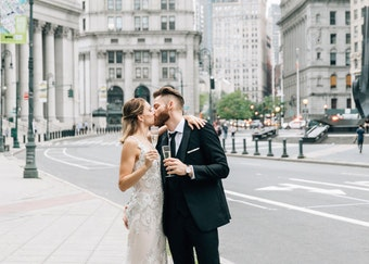 Bride and groom drinking champagne in New York City. Groom wearing generation tux.