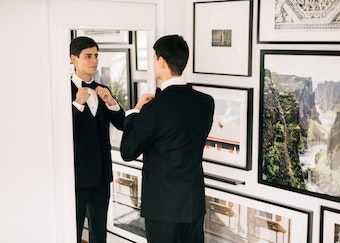 Groom straightening tie in mirror. Wearing black tuxedo.