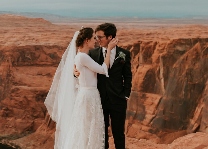 photo of a groom wearing a tuxedo and bride wearing a wedding dress with the grand canyon in the background