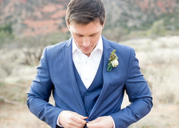 photo of young man closing the buttons on his tuxedo while wearing a blue tuxedo jacket with desert landscape in the background