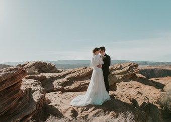 photo of a groom holding his bride wearing a black tuxedo and wedding dress with rocky desert landscape in the background