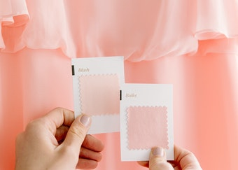 photo of a woman's hands holding suit color swatches and comparing to her bridesmaids dress color