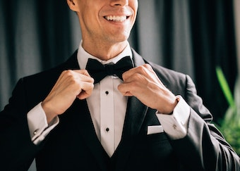 photo of a man straightening his bowtie and smiling while wearing a tuxedo