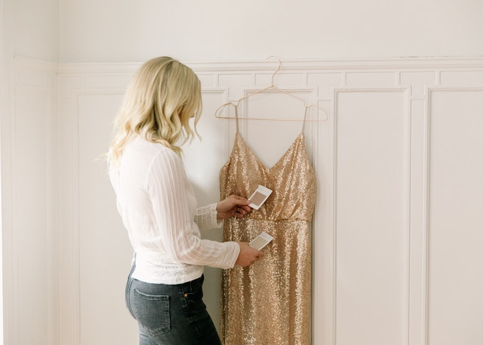 photo of a blonde woman comparing tuxedo swatches to her bridesmaids dresses