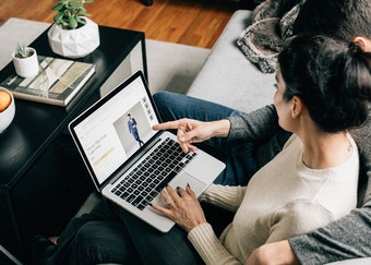 photo of a woman viewing the generation tux website on an apple laptop on the couch with her husband